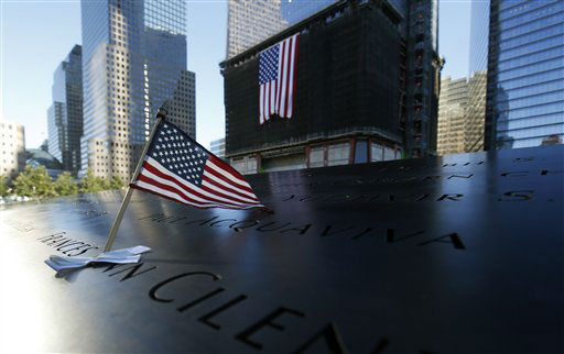 An American flag is inserted in one of the of names engraved at the north reflecting pool at the World Trade Center Memorial, during the 11th anniversary observance of the attacks at the World Trade Center, in New York, Sept. 11 2012. &#40;AP Photo&#47;Mike Segar, Reuters, Pool&#41; <span class=meta>(AP Photo&#47; MIKE SEGAR)</span>