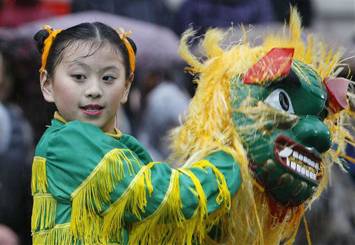 A young dancer from the Fairfax Chinese dance troupe from the Washington DC area performs in heavy rain during the annual London New Year&#39;s Day parade  Sunday, Jan. 1, 2012. &#40;AP Photo&#47;Alastair Grant&#41; <span class=meta>(AP Photo&#47; Alastair Grant)</span>