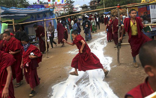 A young Buddhist monk jumps over spilled tea near the venue of the Kalachakra Buddhist festival, in the town of Bodh Gaya, believed to be the place where Buddha attained enlightenment, Bihar, India, Monday, Jan. 2, 2012. &#40;AP Photo&#47;Altaf Qadri&#41; <span class=meta>(AP Photo&#47; Altaf Qadri)</span>