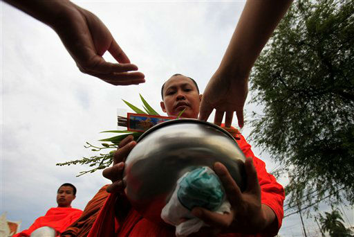 Thai Buddhists offer food to a Buddhist monk during a morning alms at Marble temple in Bangkok Monday, Jan. 2, 2012. &#40;AP Photo&#47;Sakchai Lalait&#41; <span class=meta>(AP Photo&#47; Sakchai Lalit)</span>