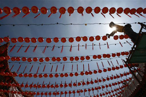 A worker hangs up Chinese traditional lanterns for the upcoming Chinese New Year of the Dragon at a temple in Kuala Lumpur, Malaysia, Monday, Jan. 2, 2012. &#40;AP Photo&#47;Lai Seng Sin&#41; <span class=meta>(AP Photo&#47; Lai Seng Sin)</span>