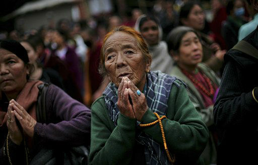 An elderly Buddhist devotee looks at a giant screen on a street, which shows the Kalachakra ritual dance live, during the Kalachakra Buddhist festival, in the town of Bodh Gaya, believed to be the place where Buddha attained enlightenment, Bihar, India, Monday, Jan. 2, 2012. &#40;AP Photo&#47;Altaf Qadri&#41; <span class=meta>(AP Photo&#47; Altaf Qadri)</span>