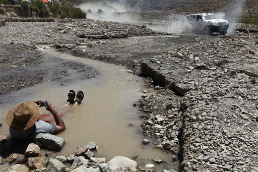 A man takes pictures as Toyota driver Abdulla Alheraiz and co-driver Khalid Ahmad, both of the United Arab Emirates, compete in the third stage of the 2012 Argentina-Chile-Peru Dakar Rally between San Rafael and San Juan, Argentina, Tuesday Jan. 3, 2012. &#40;AP Photo&#47;Frederic Le Floch,Pool&#41; <span class=meta>(AP Photo&#47; Frederic Le Floch)</span>