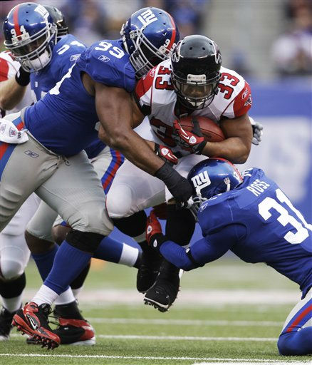 Atlanta Falcons running back Michael Turner &#40;33&#41; is tackled by New York Giants defensive tackle Chris Canty &#40;99&#41; and  Aaron Ross during the first half of an NFL wild card playoff football game Sunday, Jan. 8, 2012, in East Rutherford, N.J. &#40;AP Photo&#47;Matt Slocum&#41; <span class=meta>(AP Photo&#47; Matt Slocum)</span>