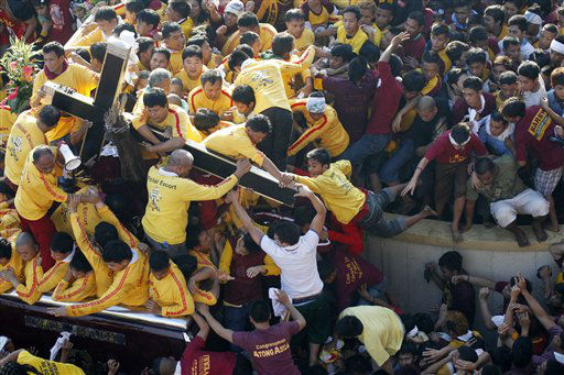 "<div class=""meta image-caption""><div class=""origin-logo origin-image ""><span></span></div><span class=""caption-text"">Barefoot Catholic devotees jostle to kiss the cross being borne by the wooden statue of the Black Nazarene as they gather at the Rizal Park Monday, Jan. 9, 2012 during it's annual festival in Manila, Philippines. More than 3 million devotees paraded the charred Christ statue, believed to have healing powers, through the Philippine capital despite a warning from President Benigno Aquino III that terrorists might target the gathering. (AP Photo/Bullit Marquez) (AP Photo/ Bullit Marquez)</span></div>"