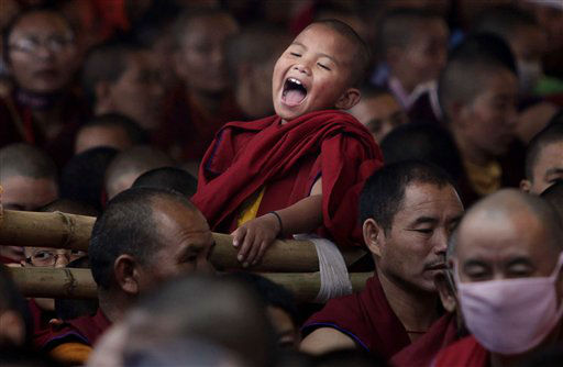 A young Buddhist monk laughs as he attends the final day of Kalachakra Buddhist festival, in the town of Bodh Gaya, believed to be the place where Buddha attained enlightenment, in the eastern state of Bihar, India, Tuesday, Jan. 10, 2012. &#40;AP Photo&#47;Altaf Qadri&#41; <span class=meta>(AP Photo&#47; Altaf Qadri)</span>