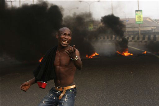 A angry youth protest in front of a burning barrier following the removal of a fuel subsidy by the government in Lagos, Nigeria, Tuesday, Jan. 10, 201. Angry youths erected a burning roadblock outside luxury enclaves in Nigeria&#39;s commercial capital Tuesday as a paralyzing national strike over fuel prices and government corruption entered its second day.&#40;AP Photo&#47;Sunday Alamba&#41; <span class=meta>(AP Photo&#47; Sunday Alamba)</span>