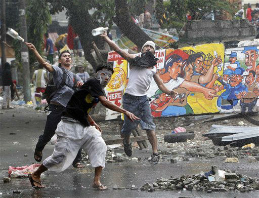 Residents throw bottles and rocks at police during a violent demolition in San Juan, east of Manila, Philippines, Wednesday Jan. 11, 2012. Several residents and police as well as demolition crew were injured as residents resist the demolition of their houses which allegedly was effected to pave the way for the development of the prime property such as the building of a new city hall, a shopping mall and condominiums. &#40;AP Photo&#47;Bullit Marquez&#41; <span class=meta>(AP Photo&#47; Bullit Marquez)</span>