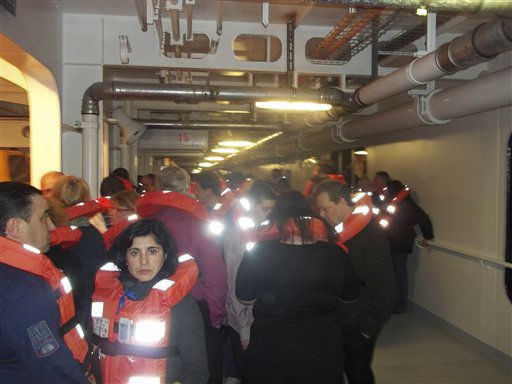 This photo acquired by the Associated Press from a passenger of the luxury ship that ran aground off the coast of Tuscany shows fellow passengers wearing life-vests on board the Costa Concordia  as they wait to be evacuated, Saturday, Jan. 14, 2012. A luxury cruise ship ran aground off the coast of Tuscany, sending water pouring in through a 160-foot &#40;50-meter&#41; gash in the hull and forcing the evacuation of some 4,200 people from the listing vessel early Saturday, the Italian coast guard said. &#40;AP Photo&#47;Courtesy from a passenger aboard the ship&#41; <span class=meta>(AP Photo&#47; Anonymous)</span>