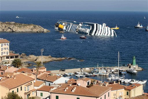 The luxury cruise ship Costa Concordia leans on its side after running aground the tiny Tuscan island of Giglio, Italy, Saturday, Jan. 14, 2012. A luxury cruise ship ran aground off the coast of Tuscany, sending water pouring in through a 160-foot &#40;50-meter&#41; gash in the hull and forcing the evacuation of some 4,200 people from the listing vessel early Saturday, the Italian coast guard said. &#40;AP Photo&#47;Gregorio Borgia&#41; <span class=meta>(AP Photo&#47; Gregorio Borgia)</span>