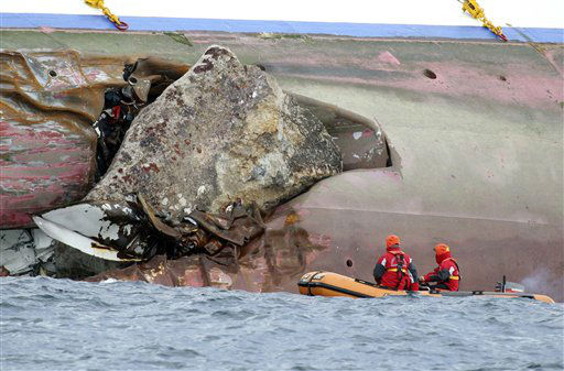 Firefighters on a dinghy look at a rock emerging from the side of the luxury cruise ship Costa Concordia, the day after it ran aground off the Tuscan island of Giglio, Italy, Sunday, Jan. 15, 2012.  The Italian Coast Guard says its divers have found two more bodies aboard the Costa Concordia. The discovery of the bodies brings to five the number of known dead after the luxury ship ran aground with some 4,200 people aboard on Friday night. &#40;AP Photo&#47;Andrea Sinibaldi, Lapresse&#41;   ITALY OUT <span class=meta>(AP Photo&#47; Andrea Sinibaldi)</span>