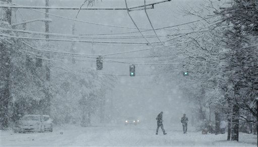 Pedestrians walk across a hill in Seattle during a snowstorm, Sunday, Jan. 15, 2012. Several inches of snow fell quickly Sunday morning, snarling traffic and clogging roadways. &#40;AP Photo&#47;Ted S. Warren&#41; <span class=meta>(AP Photo&#47; Ted S. Warren)</span>