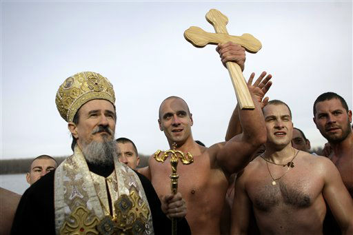 Marko Tomasevic, 31, center, lifts up a wooden cross, after being the first to reach it in a traditional cross retrieval race on the Danube river in Belgrade, Serbia, Thursday, Jan. 19, 2012. The retrieval of a cross is a traditional event that marks the Orthodox Epiphany, which according to the Julian calendar, falls on Jan. 19. &#40;AP Photo&#47; Marko Drobnjakovic&#41; <span class=meta>(AP Photo&#47; Marko Drobnjakovic)</span>