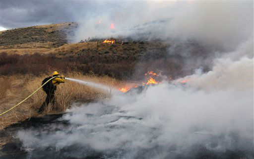 Firefighters battle a fast-moving brush fire burns in Pleasant Valley, south of Reno, Nev., on Thursday, Jan. 19, 2012. Winds gusting up to 82 mph pushed a fast-moving brush fire through a valley south of Reno on Thursday, burning several homes, threatening dozens more and forcing hundreds of residents to evacuate their neighborhoods. &#40;AP Photo&#47;Cathleen Allison&#41; <span class=meta>(AP Photo&#47; Cathleen Allison)</span>