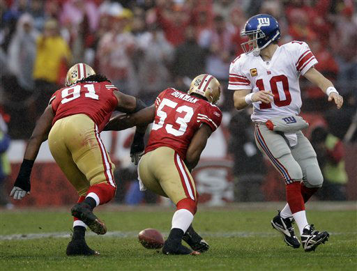New York Giants quarterback Eli Manning fumbles as he is hit by San Francisco 49ers&#39; Ray McDonald &#40;91&#41; and  NaVorro Bowman &#40;53&#41; during the first half of the NFC Championship NFL football game Sunday, Jan. 22, 2012, in San Francisco.  &#40;AP Photo&#47;David J. Phillip&#41; <span class=meta>(AP Photo&#47; David J. Phillip)</span>