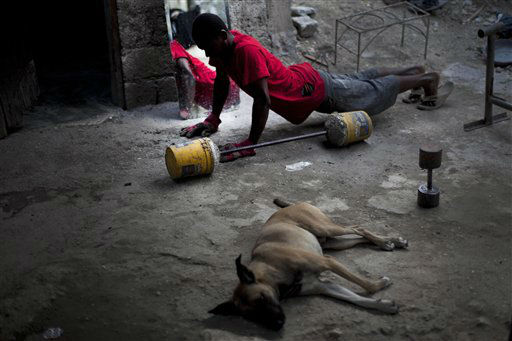 A young man exercises at the entrance of his house as his dog lies on the floor in Port-au-Prince, Haiti, Monday, Jan. 23, 2012. &#40;AP Photo&#47;Ramon Espinosa&#41; <span class=meta>(AP Photo&#47; Ramon Espinosa)</span>
