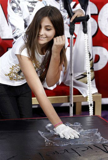 "<div class=""meta ""><span class=""caption-text "">Paris Jackson places a glove worn by her father, Michael Jackson, into the cement during the hand and footprint ceremony honoring her father in front of Grauman's Chinese Theatre in Los Angeles, Thursday, Jan. 26, 2012. The ceremony was held to celebrate the ""Michael Jackson The Immortal World Tour"" by Cirque du Soleil.  (AP Photo/Matt Sayles) (AP Photo/ Matt Sayles)</span></div>"