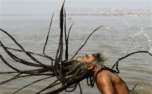 A Sadhu, or a Hindu holy man, takes a dip at Sangam, confluence of the Rivers Ganges, Yamuna and mythical Saraswati, during the annual traditional fair of Magh Mela in Allahabad, India, Monday, Jan. 30, 2012. Hundreds of thousands of devout Hindus bathe at the confluence during the astronomically auspicious period of over 45 days celebrated as Magh Mela. &#40;AP Photo&#47;Rajesh Kumar Singh&#41; <span class=meta>(AP Photo&#47; Rajesh Kumar Singh)</span>