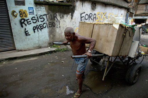 In this photo taken Jan. 31, 2012, a man pushes a cart with goods to recycle past a graffiti that reads in Portuguese &#34;We must resist&#34; in the Favela do Metro shantytown in Rio de Janeiro, Brazil. Residents of communities like Metro, located on the surroundings of the Maracana stadium, are being pushed out of their homes to make way for new roads, Olympic venues, and other projects as part of preparations to host the 2014 World Cup and the 2016 Olympics. &#40;AP Photo&#47;Victor R. Caivano&#41; <span class=meta>(AP Photo&#47; Victor R. Caivano)</span>