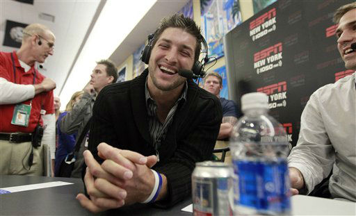Denver Broncos quarterback Tim Tebow, left, laughs during an interview on radio row at the Super Bowl XLVI media center Thursday, Feb. 2, 2012, in Indianapolis. The New England Patriots will face the New York Giants in Super Bowl XLVI Feb. 5. &#40;AP Photo&#47;David J. Phillip&#41; <span class=meta>(AP Photo&#47; David J. Phillip)</span>