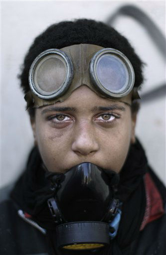 An Egyptian protestor wears a protective mask and goggles during clashes with security forces near the Interior Ministry in Cairo, Egypt, Sunday, Feb. 5, 2012. Volleys of tear gas left a white cloud over Cairo&#39;s Tahrir Square and surrounding streets in the vicinity of Egypt&#39;s Interior Ministry, in the fourth day of clashes between security forces and rock-throwing youth protesting a deadly soccer riot. &#40;AP Photo&#47;Muhammed Muheisen&#41; <span class=meta>(AP Photo&#47; Muhammed Muheisen)</span>
