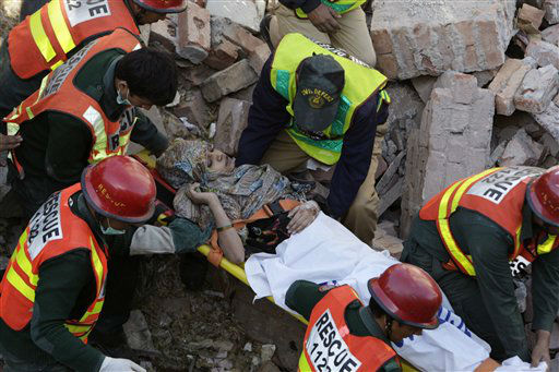 Pakistani rescue workers carry a woman who was recovered from the debris of a collapsed building in Lahore, Pakistan, Monday, Feb. 6, 2012. A three-story factory illegally set up in a residential area of Lahore collapsed Monday after several gas cylinders inside exploded, killing at least two people and trapping over 40 others in the rubble, officials said. &#40;AP Photo&#47;K.M. Chaudary&#41; <span class=meta>(AP Photo&#47; K.M. Chaudary)</span>