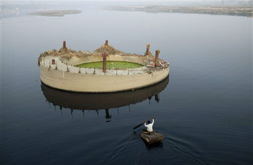 An Indian man paddles a raft to a concrete island, meant to be part of an overpass construction project but now derilect, as he searches for items to salvage in the holy River Yamuna, in New Delhi, India, Monday, Feb. 6, 2012. The Yamuna is one of the world&#39;s most polluted rivers and supplies over 60 percent of the water needed by the Delhi region. &#40;AP Photo&#47;Kevin Frayer&#41; <span class=meta>(AP Photo&#47; Kevin Frayer)</span>