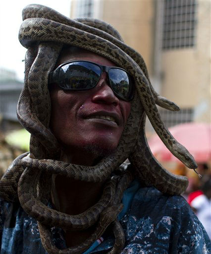 A man, carrying two snakes on his head, parades during Carnival celebrations in Jacmel, Haiti, Sunday Feb. 12, 2012. &#40;AP Photo&#47;Dieu Nalio Chery&#41; <span class=meta>(AP Photo&#47; Dieu Nalio Chery)</span>