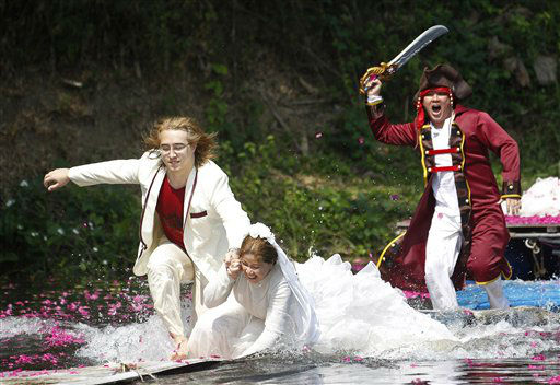 Thai-Swedish couple William Timhede, 23, left and Napatsawan Timhede, 39, are chased by an actor in pirate costume as part of an adventure-themed wedding ceremony in Prachinburi province, Thailand, Monday, Feb. 13, 2012, on the eve of Valentine&#39;s Day. &#40;AP Photo&#47;Wason Wanichakorn&#41; <span class=meta>(AP Photo&#47; Wason Wanichakorn)</span>