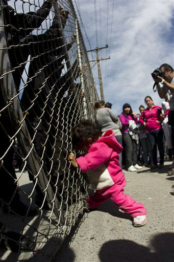 A child yells out for her father as she pushes on a gate where police stand on the other side after her mother and other adults pushed the gates in an attempt to get past state police at the Apodaca correctional state facility in Apodaca on the outskirts of Monterrey, Mexico, Sunday Feb. 19, 2012.  A fight among inmates at the prison led to a riot that killed dozens on Sunday, according to a security official. &#40;AP Photo&#47;Hans Maximo Musielik&#41; <span class=meta>(AP Photo&#47; Hans-Maximo Musielik)</span>