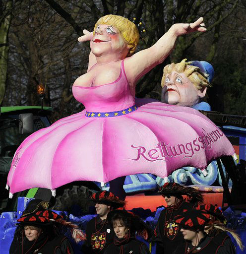 A carnival float depicting German Chancellor Angela Merkel wearing an umbrella skirt symbolizing the Europen bailout fund &#40;in German Rettungsschirm&#41; during the traditional carnival parade in Duesseldorf, western Germany, on Monday, Feb. 20, 2012. The foolish street spectacles in the carnival centers of Duesseldorf, Mainz and Cologne, watched by hundreds of thousands of people, are the highlights in Germany&#39;s carnival season on Rosemonday. &#40;AP Photo&#47;Frank Augstein&#41; <span class=meta>(AP Photo&#47; Frank Augstein)</span>