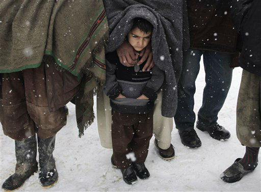 A child stands with his father as they wait to receive blankets and winter jackets from Welthungerhilfe, a German NGO, during a snow fall at a camp for internally displaced Afghans in Kabul, Afghanistan, Monday, Feb, 20. 2012. More than 40 people, most of them children, have frozen to death in what has been Afghanistan&#39;s coldest winter in years, an Afghan health official said Monday. &#40;AP Photo&#47;Musadeq Sadeq&#41; <span class=meta>(AP Photo&#47; Musadeq Sadeq)</span>