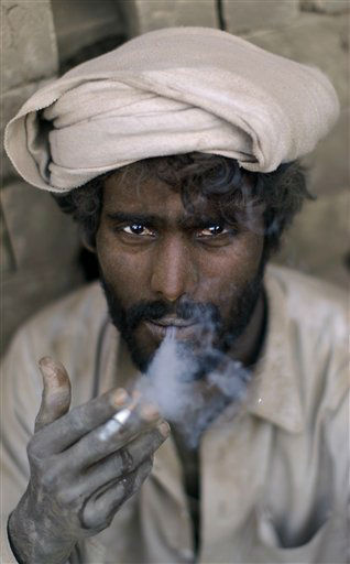 Pakistani Allah Ditta Nazar, age 35, a worker in a brick factory, smokes a cigarette while taking a break, on the outskirts of Islamabad, Pakistan, Tuesday, Feb. 21, 2012. &#40;AP Photo&#47;Muhammed Muheisen&#41; <span class=meta>(AP Photo&#47; Muhammed Muheisen)</span>