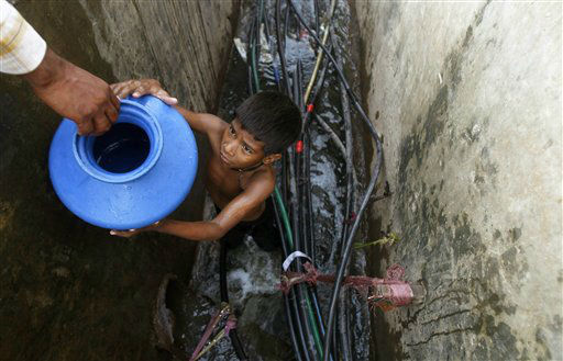A young boy collects water from a broken pipe in a slum in Mumbai, India, Wednesday, Feb. 29, 2012. Millions of children are growing up in squalid urban areas and are denied basic services despite living close to them, the United Nations Children&#39;s Fund said Tuesday. UNICEF said children living in slums and shantytowns often lack water, electricity and healthcare and urged policy makers to ensure urban planning meets the needs of children. &#40;AP Photo&#47;Rafiq Maqbool&#41; <span class=meta>(AP Photo&#47; Rafiq Maqbool)</span>