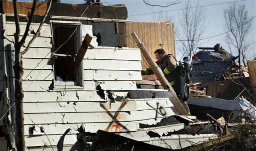 Volunteer fireman Jeff Woodyard recovers golf clubs from his father-in-law&#39;s home in Harveyville, Kan., Wednesday, Feb. 29, 2012.  A powerful storm system  lashed the Midwest early Wednesday, roughing up the country music resort city of Branson and laying waste to the small town in Kansas. &#40;AP Photo&#47;Orlin Wagner&#41; <span class=meta>(AP Photo&#47; Orlin Wagner)</span>