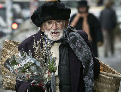 An elderly Romanian man tries to sell flowers in the streets of Bucharest, Romania, Wednesday, Feb. 29, 2012. Retirees, sometimes from villages on the outskirts of the Romanian capital, struggling on small pensions, try to take advantage of the widely spread custom of offering flowers on March 1 to celebrate the arrival of spring and make some extra money.&#40;AP Photo&#47;Vadim Ghirda&#41; <span class=meta>(AP Photo&#47; Vadim Ghirda)</span>