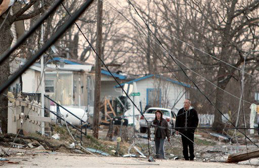 Residents walk amid downed power lines in their neighborhood in Branson, Mo, Wednesday, Feb.  29, 2012.  A powerful storm system  lashed the Midwest early Wednesday, roughing up the country music resort city of Branson and laying waste to a small town in Kansas.&#40;AP Photo&#47;Mark Schiefelbein&#41; <span class=meta>(AP Photo&#47; Mark Schiefelbein)</span>