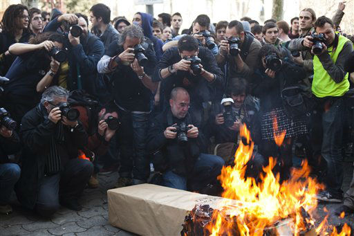 Press photographers take photos of a fake coffin representing the public education system during a demonstration in Barcelona, Spain, Wednesday, Feb. 29, 2012. Spanish students in Barcelona clashed Wednesday with police and set fire to garbage containers during nationwide protests against education spending cuts. &#40;AP Photo&#47;Marta Ramoneda&#41; <span class=meta>(AP Photo&#47; Marta Ramoneda)</span>