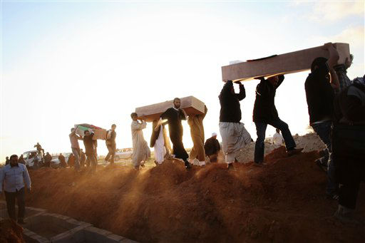Libyan men carry coffins of victims, discovered in a mass grave, at a funeral in Benghazi, Libya, Monday, March 5, 2012. Thousands of mourners gathered Monday in the eastern Libyan city of Benghazi to bury 155 bodies unearthed from a mass grave of people were killed during last year&#39;s civil war. It was the largest grave yet to be discovered from the conflict that began as a popular uprising and ended with the capture and killing of Libyan leader Moammar Gadhafi last October.&#40;AP Photo&#47;Manu Brabo&#41; <span class=meta>(AP Photo&#47; Manu Brabo)</span>