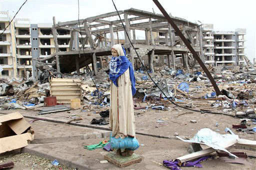 A statue of the Virgin Mary is all that remains of the St. Louis Catholic church, after a series of deadly explosions at a munitions depot devastated adjacent residential neighborhoods, killing at least 246 people, in Brazzaville, Republic of Congo Wednesday, March 7, 2012. Seen behind the statue are a new church building, center, and social housing, rear. Both were under construction at the time of the explosions. More than three days have passed since a catastrophic explosion laid waste to a section of the Republic of Congo&#39;s capital, and officials confirmed that as of Wednesday that no coordinated rescue effort had been launched, making it increasingly unlikely that any more people will be pulled alive from the flattened houses.&#40;AP Photo&#41; <span class=meta>(AP Photo&#47; STR)</span>