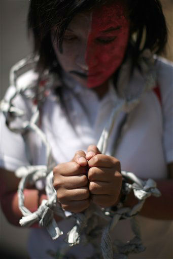"<div class=""meta ""><span class=""caption-text "">A woman with chains made with paper around her wrists protests against violence against women during an event marking the International Women's Day in Mexico City, Thursday March 8, 2012. (AP Photo/Alexandre Meneghini) (AP Photo/ Alexandre Meneghini)</span></div>"