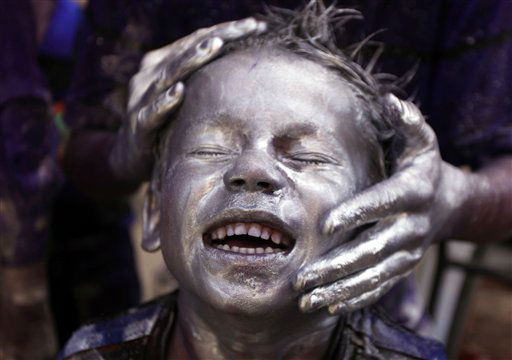 A young Indian boy is smeared with colored powder and glitter on his face during Holi celebrations in Allahabad, India, Friday, March 9, 2012. Holi, the Hindu festival of colors, also heralds the coming of spring. &#40;AP Photo&#47;Rajesh Kumar Singh&#41; <span class=meta>(AP Photo&#47; Rajesh Kumar Singh)</span>
