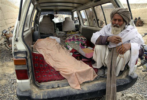 An elderly Afghan man sits next to the covered body of a person who was allegedly killed by a U.S. service member, in a minibus in Panjwai, Kandahar province south of Kabul, Afghanistan, Sunday, March 11, 2012. A U.S. service member walked out of a base in southern Afghanistan before dawn Sunday and started shooting Afghan civilians, according to villagers and Afghan and NATO officials. Villagers showed an Associated Press photographer 15 bodies, including women and children, and alleged they were killed by the American. &#40;AP Photo&#47;Allauddin Khan&#41; <span class=meta>(AP Photo&#47; Allauddin Khan)</span>