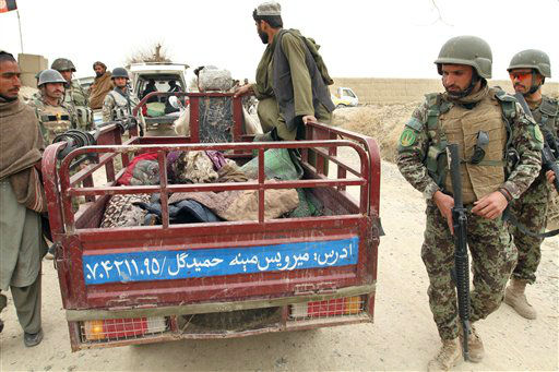 In this Sunday, March 11, 2012 photo, Afghan soldiers and civilians gather around a truck carrying bodies of civilians allegedly killed in a shooting rampage by a U.S. soldier in Panjwai, Kandahar province south of Kabul, Afghanistan. The United States has paid &#36;50,000 in compensation for each Afghan killed and &#36;11,000 for each person wounded in the shooting spree allegedly committed by a U.S. soldier in southern Afghanistan, an Afghan official and a community elder said Sunday. The sums, much larger than typical payments made by the U.S. to families of civilians killed in military operations in Afghanistan, come as the U.S. tries to mend relations following the killing rampage that has threatened to undermine the international effort here. &#40;AP Photo&#47;Allauddin Khan&#41; <span class=meta>(AP Photo&#47; Allauddin Khan)</span>