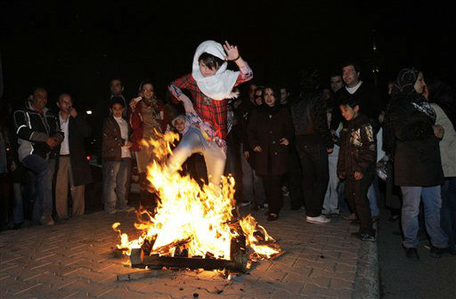 An Iranian woman jumps over a bonfire, in the Pardisan Park in Tehran, Iran, Tuesday, March 13, 2012, during Chaharshanbe Souri, or Wednesday Feast, an ancient Festival of Fire, on the eve of the last Wednesday of the year. Iranians jump over burning bonfires while throwing firecrackers, celebrate arrival of the spring which coincides with Iranian new year, or Nowruz. Setting off firecrackers has turned into careless massive explosions in the recent years, which leaves many wounded every year, prompting strong reactions by police. The festival, came from pre-Islamic Zoroastrianism era, has been discouraged by conservative Islamist rulers after 1979 Islamic Revolution, but without any success. &#40;AP Photo&#47;Vahid Salemi&#41; <span class=meta>(AP Photo&#47; Vahid Salemi)</span>