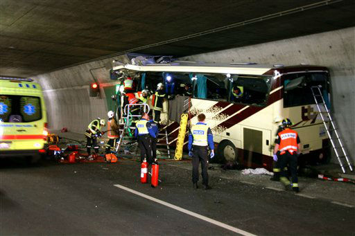Rescuers and police work amid the wreckage of a tourist bus from Belgium at the accident site in a tunnel of the A9 highway near Sierre, western Switzerland, early Wednesday, March 14, 2012. A bus carrying Belgian students returning from a ski holiday crashed into a wall in a Swiss tunnel, killing 22 Belgian 12-year-olds and six adults, police said Wednesday.  &#40;AP Photo&#47;KANTONSPOLIZEI WALLIS&#47;POLICE OF VALAIS, Handout&#41;  MANDATORY CREDIT <span class=meta>(AP Photo&#47; Anonymous)</span>