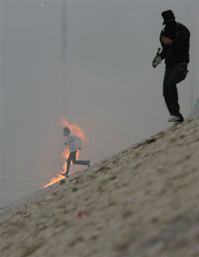 Bahraini anti-government protesters, one carrying a Molotov cocktail, run down from a main highway past the fire of a Molotov as tear gas fills the dusty air Sunday, March 18, 2012, in Muqsha, Bahrain, just outside the capital of Manama. Clashes erupted in the midst of a strong dust storm after the politically charged funeral for Jaffar al-Muwali, 41, one of two deaths Saturday that the opposition blames on excessive tear gas. &#40;AP Photo&#47;Hasan Jamali&#41; <span class=meta>(AP Photo&#47; Hasan Jamali)</span>