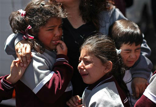 A woman comforts crying children outside a school in the Roma neighborhood after they were evacuated during the earthquake that was felt in Mexico City, Tuesday March 20, 2012.  A strong, long earthquake with epicenter in Guerrero state shook central southern Mexico on Tuesday, swaying buildings in Mexico City and sending frightened workers and residents into the streets. &#40;AP Photo&#47;Alexandre Meneghini&#41; <span class=meta>(AP Photo&#47; Alexandre Meneghini)</span>
