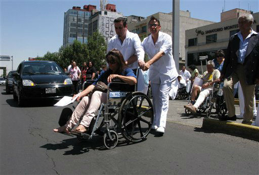 Patients are evacuated in wheelchairs from the Hospital de Chalpultepec after an earthquake was felt in Mexico City, Tuesday March 20, 2012.  A strong, long earthquake with epicenter in Guerrero state shook central southern Mexico on Tuesday, swaying buildings in Mexico City and sending frightened workers and residents into the streets. &#40;AP Photo&#47;Marco Ugarte&#41; <span class=meta>(AP Photo&#47; Marco Ugarte)</span>