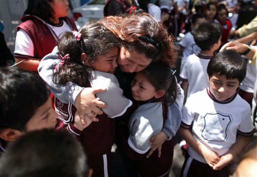 "<div class=""meta ""><span class=""caption-text "">A woman comforts her children outside a school at the Roma neighborhood after a earthquake felt in Mexico City Tuesday March 20, 2012.  A strong, long earthquake with epicenter in Guerrero state shook central southern Mexico on Tuesday, swaying buildings in Mexico City and sending frightened workers and residents into the streets..(AP Photo/Alexandre Meneghini) (AP Photo/ Alexandre Meneghini)</span></div>"